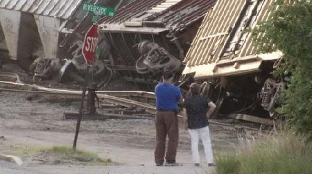 Two people look at the train cars that derailed in Rumford on Friday.