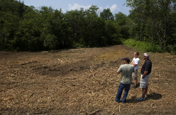 Jeremy Guerrette (from left), Dustin Ramsay, and Mike Bisson look over a recently cleared area on July 23 that will soon be part of the Reeds Brook Trails in Hampden.
