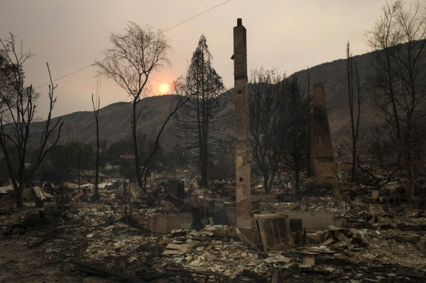 The remnants of homes that were destroyed by the Carlton Complex Fire are seen from the road in Pateros, Washington, on Friday. Officials said Saturday that 100 homes have been destroyed by the fire.