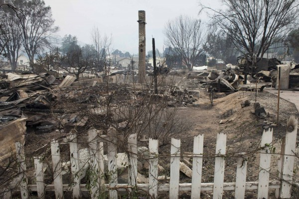 The remnants of a neighborhood that was consumed by the Carlton Complex Fire are seen from the road in Pateros, Washington, on Friday. Officials said Saturday that 100 homes have been destroyed by the fire.