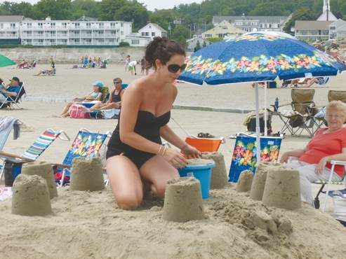 A builder stands at top Murphy's Castle, one of nearly 50 entries in the Ogunquit Parks and Recreation Sand Castle Contest this past weekend.