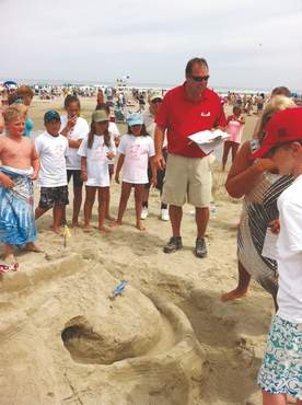 Ogunquit Select Board member Gary Latulippe, in red, judging the eventual winner of the Ogunquit Parks and Recreation Sand Castle Contest in the children's division.
