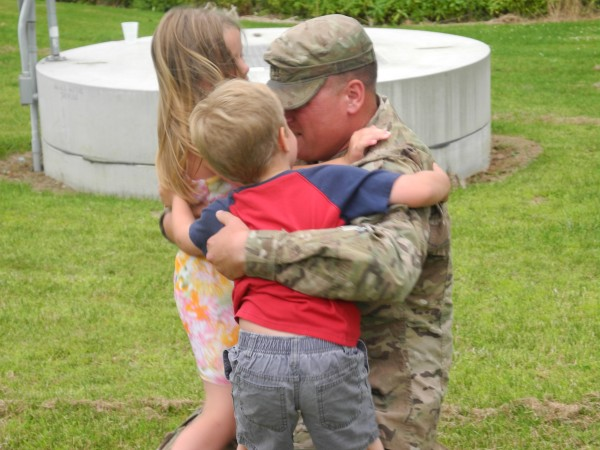 Maine Army National Guard Spc. Travis Ellsworth embraces children Aryana, 7, and Jayden, 5, at an emotional reunion Wednesday evening at the Faith Temple Church of God in Belfast.
