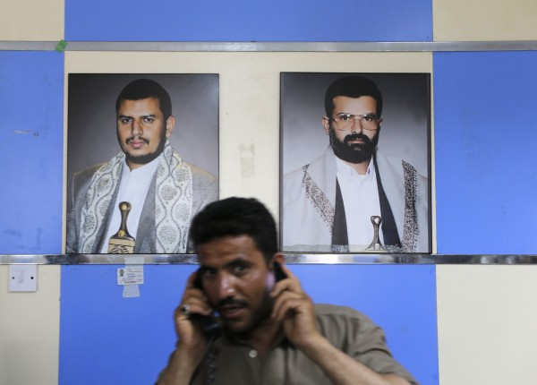 A man uses a phone in front of posters of the leader of the Shiite Muslim al-Houthi group, Abdul-Malik al-Houthi (left), and the group's founder Houssein al-Houthi at the entrance of the group's political headquarters in Sanaa last month.