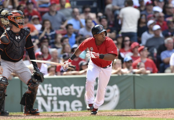 Boston Red Sox pinch hitter Jonathan Herrera (10) hits a walk off single during the ninth inning in game one against the Baltimore Orioles at Fenway Park on Saturday.