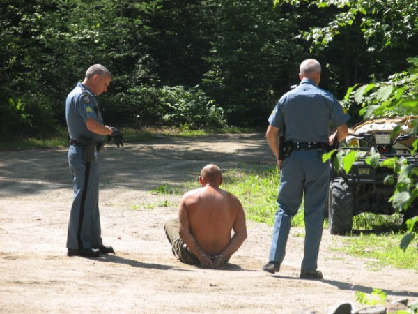 Sgt. Alden Bustard (left) and Sgt. Tim Varney (right) of the Maine State Police stand on either side of a man taken into custody in connection with a reported stabbing Wednesday morning in Sullivan.