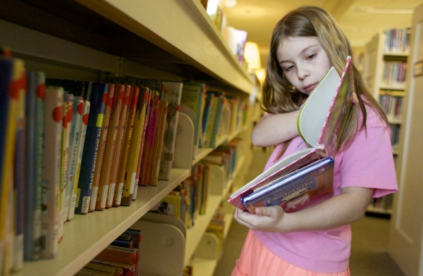 Ingrid Schaefer, 8, looks through books at the Bangor Library in this May 2014 file photo.