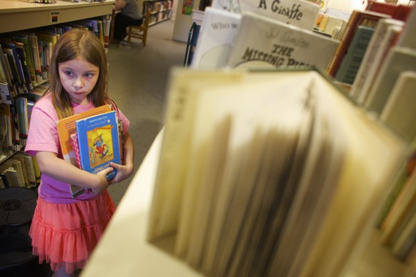 Ingrid Schaefer, 8, looks selects books at the Bangor Library in this May 2014 file photo.