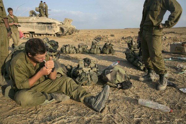 An Israeli soldier smokes a cigarette after crossing back into Israel from Gaza July 28, 2014. Israel eased its assaults in the Gaza Strip and Palestinian rocket fire from the enclave declined sharply on Monday, the military said, with both the U.S. and United Nations calling for a durable ceasefire.