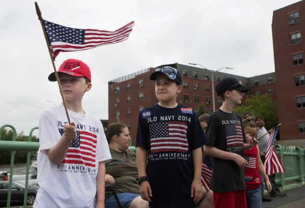 Caleb Gould (left), 9, waves his flag with Bradley Molloy (center), 11, and Benjimin Gould, 12, during the annual Fourth of July parade Friday.