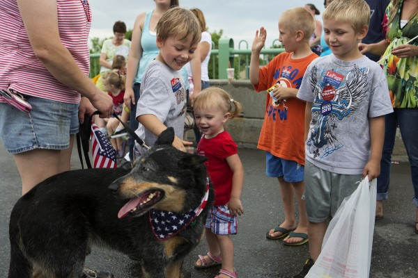 Aaron Wentworth (left), 5, and Alyssa Wentworth (second from left), 1, pet a dog in the parade while Logan Stevenson (right), 3, watches during the annual parade.