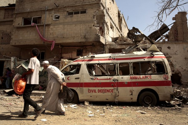 Men walk past a destroyed ambulance at the start of a 12-hour cease-fire, as people scour the rubble of their homes in the Shejaiya neighborhood of Gaza City, looking for the dead and recovering belongings.