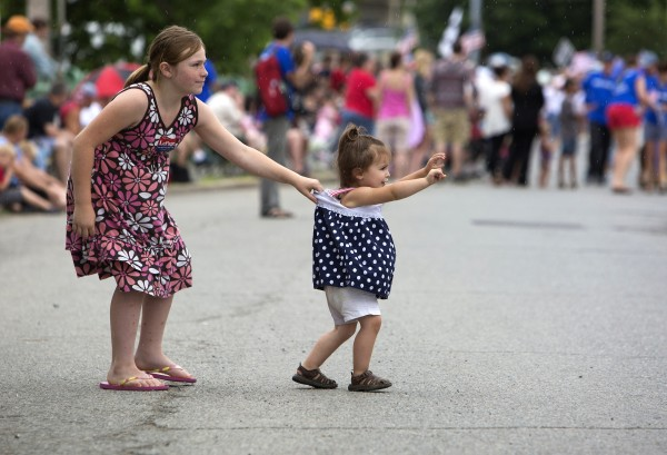 Aliyah Malcolm (left), 9, stops her younger sister, Emma Malcolm, 2, from walking into the parade.