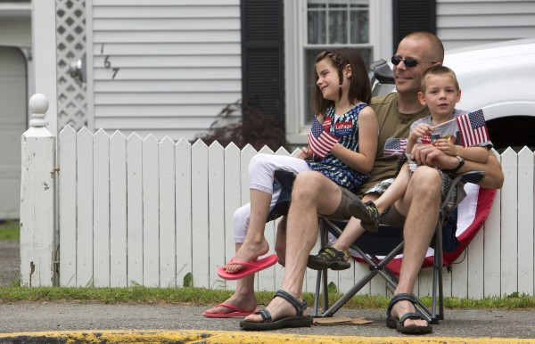 (From left) Teagan Fournier, 8, Gene Fournier, and Connor Fournier, 5, watch the annual Fourth of July parade Friday. Despite the chance of rain, many people came out to watch the parade that started in Brewer and traveled into downtown Bangor.