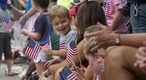 Kaiden Phillips, 2, giggles after getting a kiss from Gretta Phillips during the annual Fourth of July parade Friday.