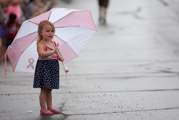 Audrina Stimus, 2, waves to people in the parade from under her umbrella. Despite the chance of rain, many people came out to watch the Fourth of July parade.