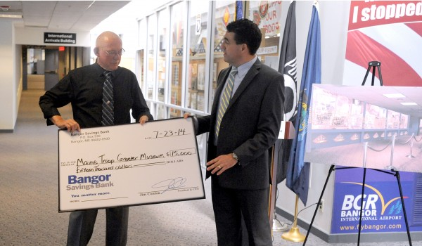 Charles Knowlen, left, chairman of the Maine Troop Greeters, receives a ceremonial check from Bob Montgomery-Rice, the executive vice president and chief operating officer of Bangor Savings Bank. The group received a donation of $15,000 from Bangor Savings Bank.
