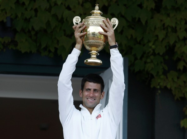 Novak Djokovic of Serbia holds the winner's trophy on the clubhouse balcony after defeating Roger Federer of Switzerland  in their men's singles final tennis match at the Wimbledon Tennis Championships Sunday in London.