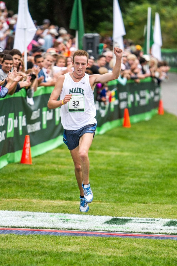 Former Bangor High School star Riley Masters raises his fist as he crosses the finish line as the first Maine men's finisher in the Beach to Beacon 10K road race in Cape Elizabeth in this August 2013 file photo.