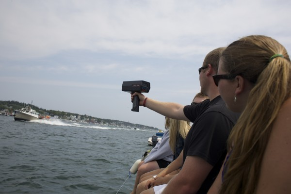 Ben Walls uses a radar gun to track speeds during the 2014 lobster boat races on Sunday in Stonington. The fastest boat of the day was clocked at 47.4 mph.