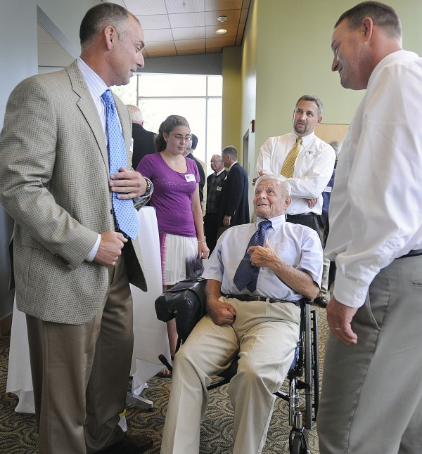 Mike Bordick , left and Dan Kane, right, spend a few minutes with John Winkin at a tribute to him and his coaching career on June 28, 2009 at the University of Maine in Orono. Dr Winkin is accompanied by his son David and his granddaughter Bethany.