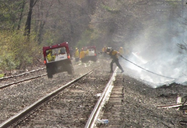 A firefighter drags hose from a tanker truck parked nearby, through a wooded area and onto an otherwise remote section of railroad tracks in Old Orchard Beach on May 8, 2014. A freight train spitting sparks was blamed for a string of brush fires along the tracks that continued through five southern Maine towns.