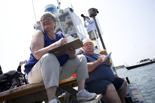 Judges Susan Soper (left) and Keith Young watch the finish line of a race during the 2014 lobster boat races on Sunday in Stonington.