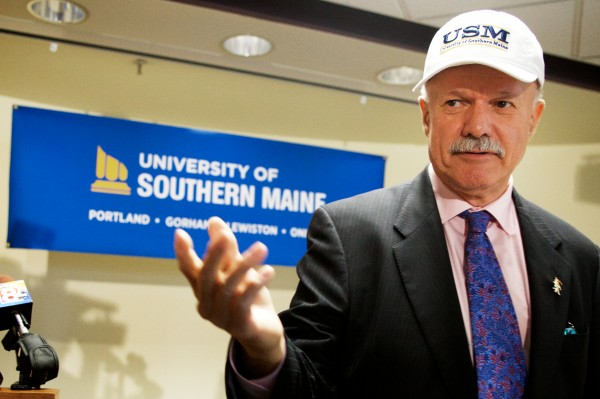 David Flanagan, the retired CEO of Central Maine Power Co. and a former University of Maine System trustee, dons a USM cap after being named the interim president at the troubled University of Southern Maine on Wednesday in Portland.
