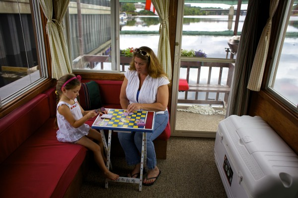 From left, Lily Wilcox, 5, plays a game with Tory Armstrong on her houseboat &quotLily's Pad&quot on the Bangor Waterfront.