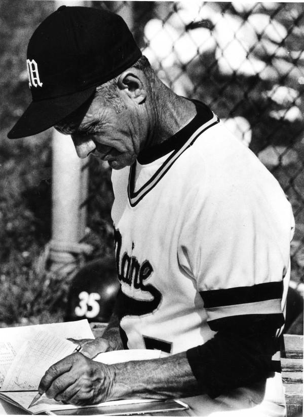 Maine baseball coach John Winkin checks his scorebook during a game on June 9, 1984. Winkin died Saturday at age 94.