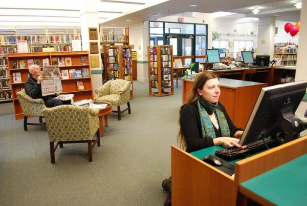 Kristina Skillin (right) searches for books while John Bonnell reads the newspaper at Falmouth Memorial Library in this 2012 file photo.