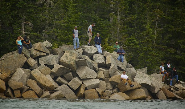 Spectators of the 2014 lobster boat races climb on rocks along the track to watch the finish line on Sunday in Stonington.