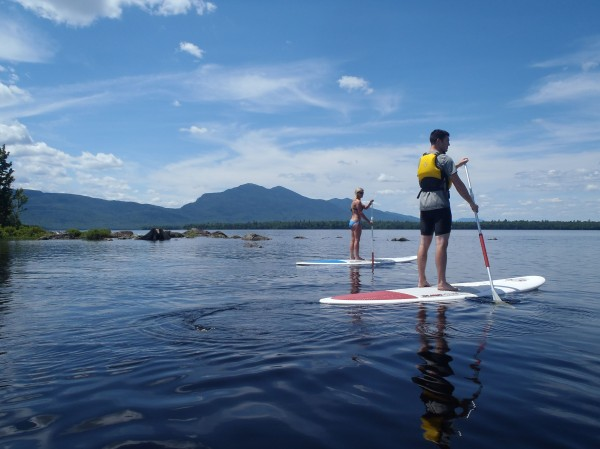 Maine registered guide Lani Cochrane (left), recreational programs manager for Maine Huts & Trails, teaches Derek Runnells of Brewer how to stand-up paddle board on Flagstaff Lake on July 12, 2014. Stand up paddle boarding is just one of the many outdoor activities available to guests at the Maine Huts & Trails huts.