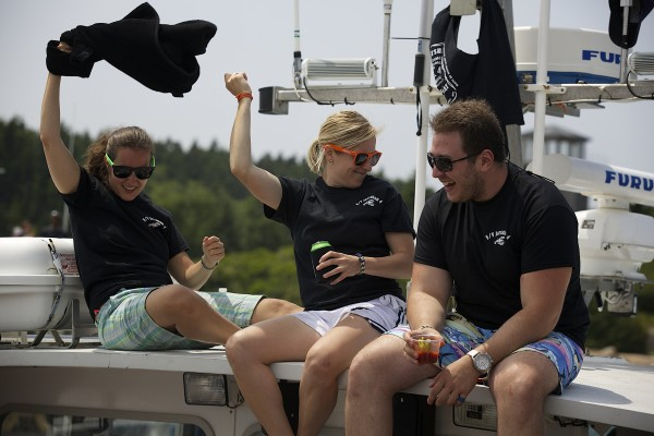 Emily Kaplan (left), Erin Polselli (center) and Rod Raykhman dance on top of the Jarsulan 4 during the 2014 lobster boat races on Sunday in Stonington.