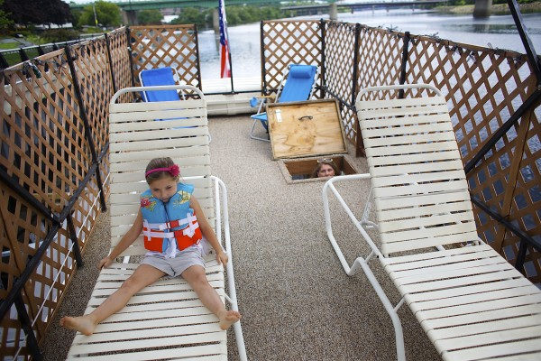 From left, Lily Wilcox, 5, plays on the top deck of Tory, right, and Guy Armstrong's houseboat, which they keep docked on the Bangor Waterfront throughout the summer months.