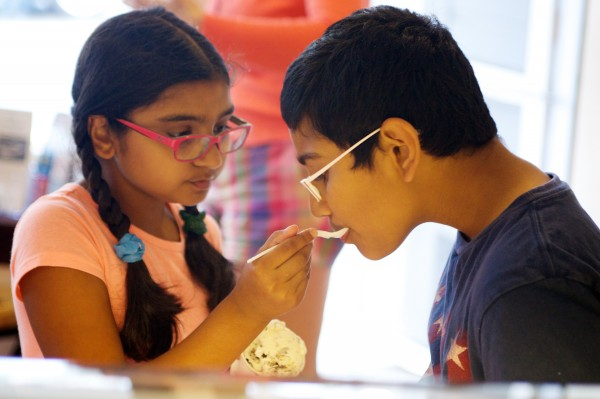 Dhanya Chasmawala, 8, gives her big brother Gautam, 11, a taste of her ice cream at Rococo Artisan Ice Cream in Kennebunkport.
