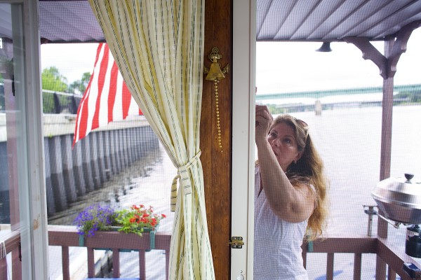 Tory Armstrong unlocks a door on the houseboat she and her husband Guy are keeping docked on the Bangor Waterfront throughout the summer months.