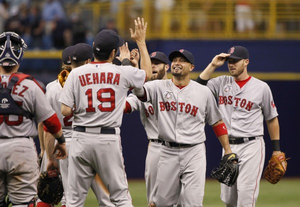 Boston Red Sox right fielder Shane Victorino (18) and relief pitcher Koji Uehara (19) and teammates high five after they beat the Tampa Bay Rays at Tropicana Field in St. Petersburg, Florida, Sunday. Boston won 3-2.
