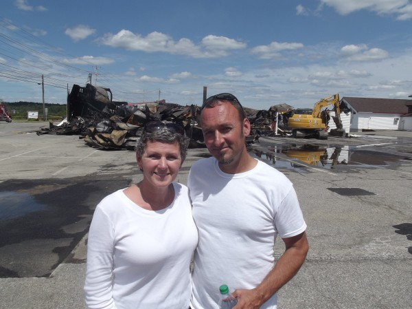 David and Julie Barker manage to smile despite the fire that reduced their landmark Machias business, Helen's Restaurant, to smoldering rubble in the background. They plan to rebuild.