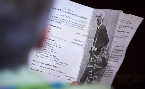 A church goer reads the program at the Unitarian Universalist Society in Bangor during a Sunday service for the 30th anniversary of the death of Charlie Howard.
