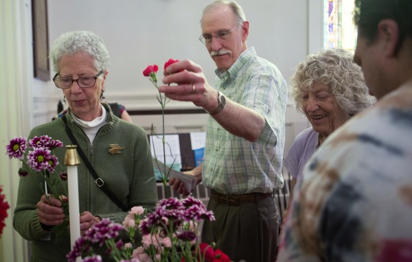 Mary Phillips (left) and Michael Howard (center) select flowers to be dropped into the Kenduskeag Stream after a church service on Sunday at the Unitarian Universalist Society in Bangor to remember the 30th anniversary of the death of Charlie Howard.