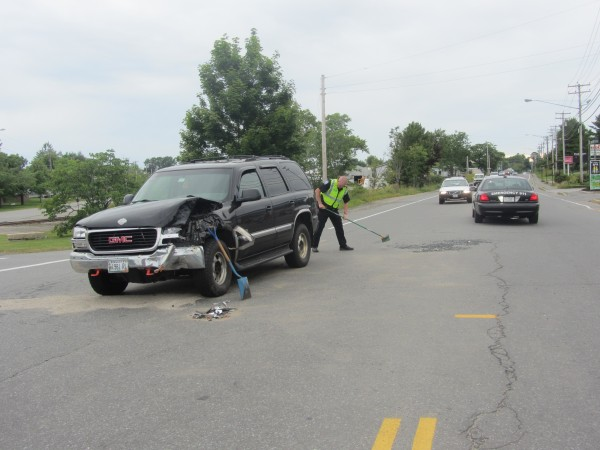 Rockland Police Sgt. Matthew Lindahl cleans up debris from a two-car crash Sunday afternoon in Rockland.