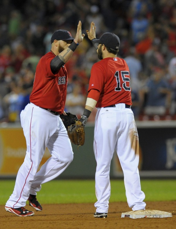Boston Red Sox left fielder Jonny Gomes (5) high fives second baseman Dustin Pedroia (15) after defeating the Kansas City Royals at Fenway Park in Boston Saturday night.