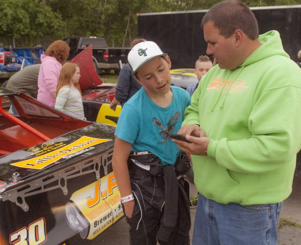 Dylan Street of Old Town is only 12 years old, but he is racing in the Sport Four division at Speedway 95. Dylan stands with his father Jeff Street and their No. 30 car in his pit area before races Saturday, July 5, 2014 at Speedway 95, Hermon, Maine.