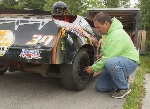 Dylan Street's father Jeff Street rechecks the tire pressure and lug nuts on the wheels of car No. 30 in their pit area before races Saturday, July 5, 2014, at Speedway 95, Hermon, Maine.