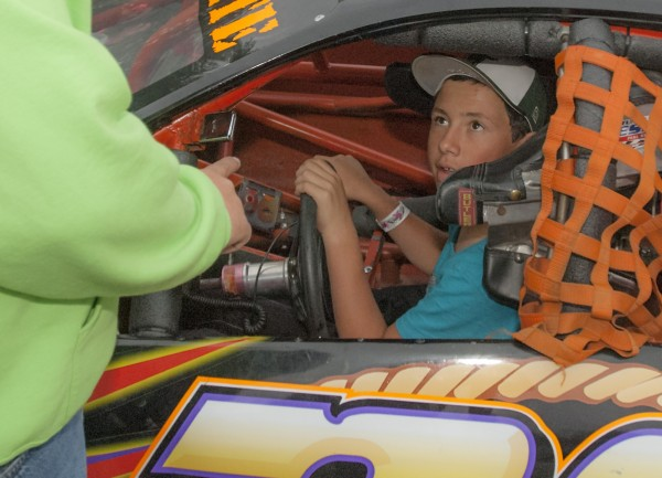 Dylan Street of Old Town is only 12, but he is racing in the Sport Four division at Speedway 95. Dylan listens to his father Jeff Street for directions in his pit area before races Saturday, July 5, 2014 at Speedway 95, Hermon, Maine.