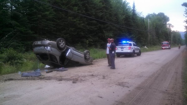 A vehicle sits on its roof after a rollover accident in Rangeley Plantation on Sunday. The driver swerved to avoid a moose.