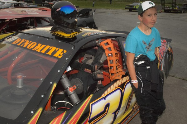 Twelve-year-old Dylan Street of Old Town stands with his car in his pit area before races begin Saturday, July 5, 2014 at Speedway 95, Hermon, Maine.