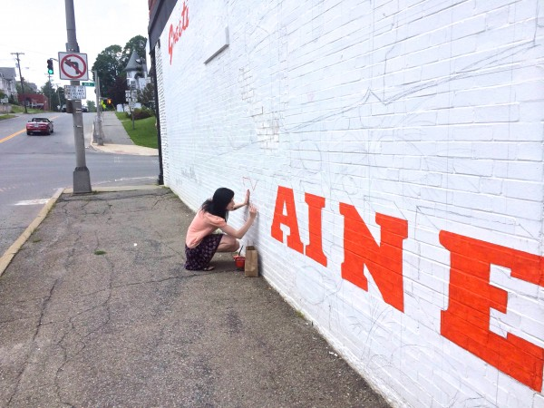 Kristen Hart, 21, of Newburgh, paints the &quotM&quot in &quotGreetings from Bangor, Maine&quot on a mural designed by Annette Dodd, co-owner of the Rock and Art Shop in Bangor, on July 25, 2014, on the wall of the brick building at 152 Main Street in downtown Bangor, which houses the Main Tavern.