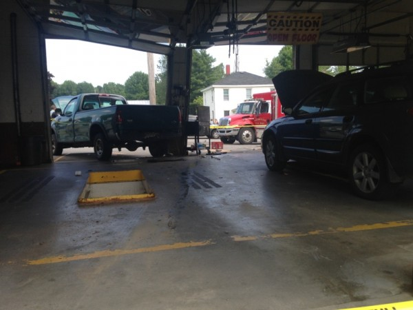 Waterville police and fire officials investigate an accident at an oil-change facility on Kennedy Memorial Drive on Tuesday morning.
